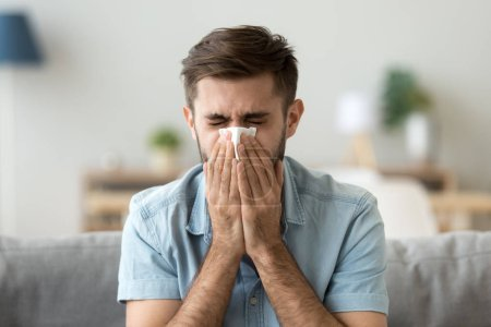 Photo for Ill young man sneezing in handkerchief blowing wiping running nose, sick allergic guy caught cold got flu influenza hay fever coughing, having seasonal allergy symptoms respiratory contagious disease - Royalty Free Image