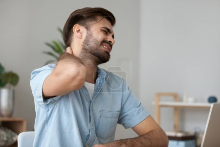 Photo for Upset man in pain touching stiff neck suffering from fibromyalgia massaging tensed muscles to relieve back joint shoulder ache tired after long sedentary computer work in incorrect posture concept. - Royalty Free Image