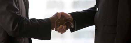Photo pour Image panoramique noir et caucasien partenaires d'affaires hommes d'affaires serrant la main à la réunion montrent le respect. Partenariat confiance concept de salutation. Bannière photo horizontale de gros plan pour la conception d'en-tête de site Web - image libre de droit