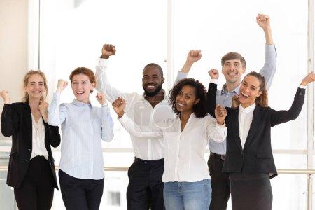 Photo pour Équipe multinationale affaires heureux célèbre victoire succès au travail se sent excité, lève les mains poings Oui geste appréciant la grande victoire. Danse de la victoire, réalisation incroyable, notion de triomphe - image libre de droit