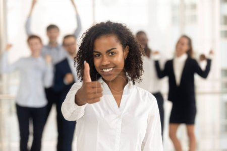 Photo for Headshot smiling african female looking at camera showing thumbs up overjoyed diverse employees in background. Leadership, successful career, client received best services and recommendation concept - Royalty Free Image