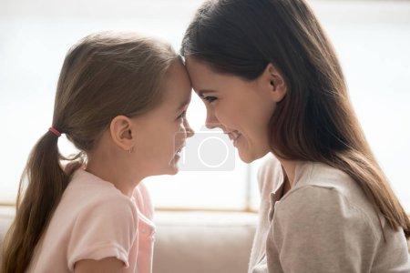 Photo pour Heureuse petite fille mignonne et souriante jeune mère touchant tendrement les fronts, aimant maman et fille enfant s'amusant à jouer coller, concept d'affection de connexion amoureuse familiale, vue de profil latérale - image libre de droit