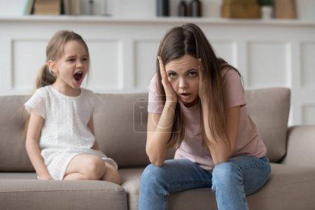 Photo pour Stressé mère épuisée, regardant la caméra se sentir désespérée sur les accès de colère de la fille enfant têtu, contrarié, ennuyée maman fatigué de fille vilain enfant difficile de crier se conduisent mal crier pour attirer l'attention - image libre de droit