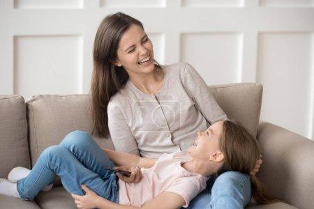 Photo pour Heureux petit enfant famille fille et la maman rire téléphone holding s'amuser avec smartphone assis sur le canapé, joyeuse mère avec enfant fille jouer avec téléphone portable Profitez de passent du temps avec gadget à la maison - image libre de droit