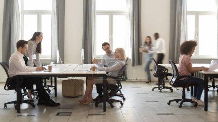 Photo pour Employés d'entreprise multiculturels occupés assis à des bureaux travaillant sur des ordinateurs dans la ruée vers les bureaux modernes, le personnel des entreprises les travailleurs de l'entreprise se déplaçant parler dans la grande entreprise de coworking open space room - image libre de droit