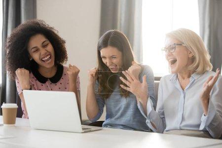 Photo pour Divers heureux heureux réjouis jeunes et vieux employés féminins équipe excitée par le résultat d'affaires de récompense de victoire en ligne, femmes d'affaires motivées gagnantes célèbrent la victoire en regardant l'écran d'ordinateur portable atteint un nouvel objectif - image libre de droit