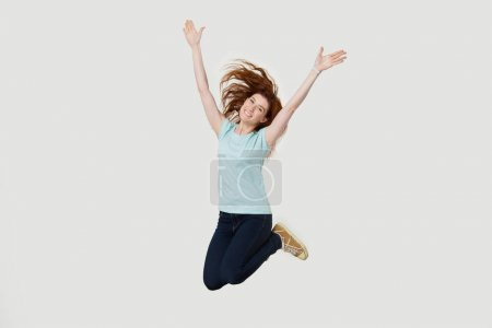 Photo for Excited cheerful young red-haired girl isolated on grey studio background jumping high raising hands up, happy smiling redhead woman in casual clothes have fun feeling free celebrating success - Royalty Free Image