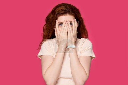 Photo for Scared red-haired young woman isolated on pink studio background hide behind hands, terrified redhead girl cover face peeping looking through fingers, curious female feel afraid peeking - Royalty Free Image