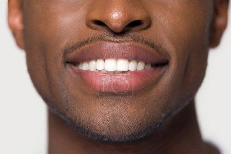 Photo pour Gros plan image recadrée africaine attrayant jeune homme visage partie ayant ultra neige blanc sourire dents droites en bonne santé isolé sur fond gris mur. Soins dentaires santé buccodentaire blanchissant concept de dentisterie - image libre de droit