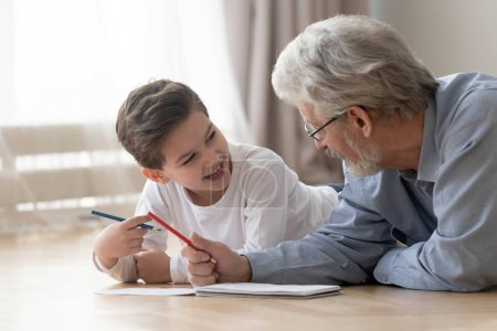 Photo for Smiling little boy lying on floor having fun enjoy painting in album together with loving grandfather, grandparent spend time teaching drawing picture entertaining at home with excited small grandson - Royalty Free Image