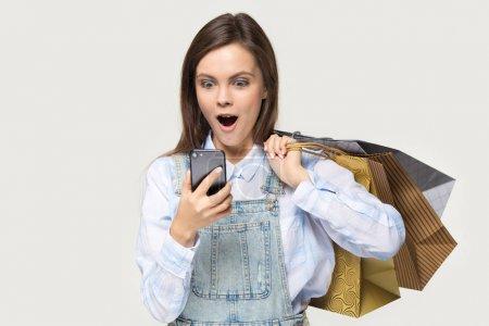 Photo pour Surpris femme heureuse détient tas sacs à provisions en papier regarde téléphone écran lire sms vendre magasin de promotion isolé sur fond gris, achat en ligne, vente de liquidation, dépenser de l'argent dans le concept d'Internet - image libre de droit