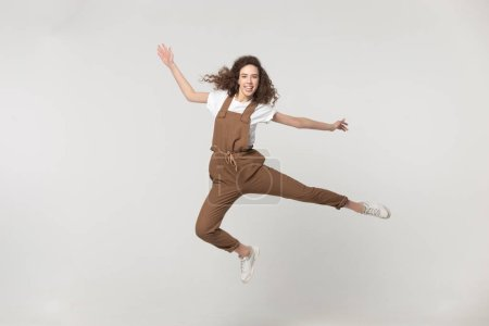 Photo for Full length overjoyed young brown-haired woman wearing jumpsuit look at camera jumping feels happy, childish girl having fun, celebrate success achievement moving in studio isolated on grey background - Royalty Free Image