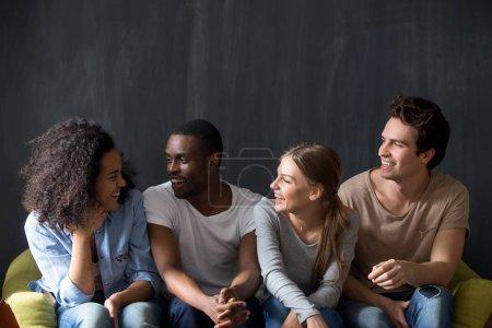 Photo pour Jeunes amis heureux et diversifiés assis ensemble sur le canapé, écoutant des filles souriantes biraciales plaisanter, rire, s'amuser ensemble. Mixte gens millénaires race bavarder, profiter du temps libre . - image libre de droit