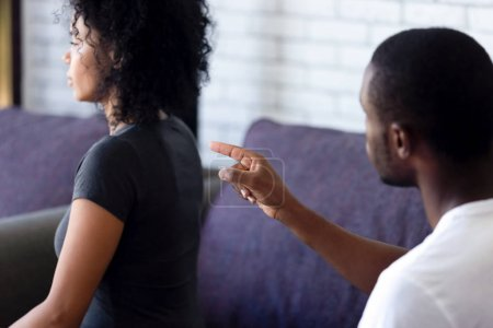 Photo for Rear view african couple sitting on sofa at home quarrelling, husband boyfriend accuse shouting screaming on wife girlfriend express complaint feels angry. Conflict situations divorce break up concept - Royalty Free Image