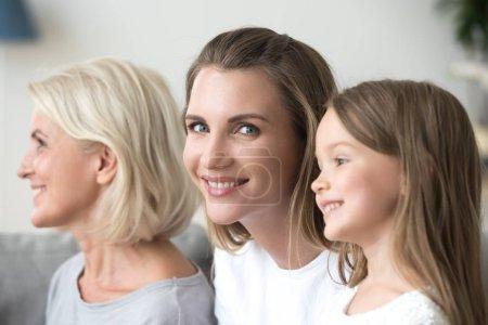 Foto de Foto de la cabeza de tres generaciones diversas madre y abuela sonriendo sentadas en el interior, se centran en la mujer milenaria en el medio. Feliz familia amistosa mejores amigos personas relativas - Imagen libre de derechos