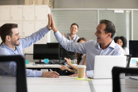 Photo pour Heureux collègues masculins excités donnant cinq au travail, célébrant le succès de l'entreprise, équipe de travailleurs de bureau applaudissent, bons résultats du travail d'équipe, réalisation de l'entreprise, satisfait, motivé par la victoire - image libre de droit
