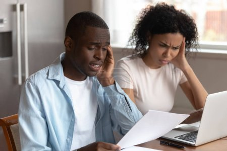 Photo for African frown couple sit at table in kitchen at home use computer online e-banking read document, overspending or debt, bankruptcy notice letter, having financial problems, check bills feels troubled - Royalty Free Image