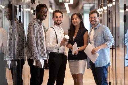 Photo pour Heureuse équipe multiethnique professionnelle d'affaires d'entreprise debout ensemble dans le couloir de bureau, souriant groupe de travail de diverses personnes confiantes regardant la caméra, quatre travailleurs internationaux portrait du personnel - image libre de droit