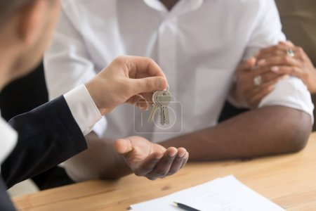 Photo for Cropped close up image african married couple owners get keys to house from realtor real estate agent, first time new home buyers, good profit deal, mortgage loan approval, moving relocation concept - Royalty Free Image