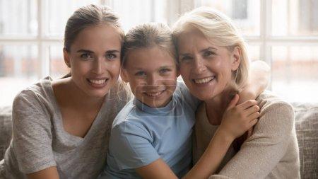 Photo pour Famille relative de personnes s'asseyent sur le divan les femmes multigénérationnelles embrassant se sentant heureux passent le temps ensemble, fille de mère et fille d'école d'enfant trois générations différentes aiment le soin et le concept de dévotion - image libre de droit