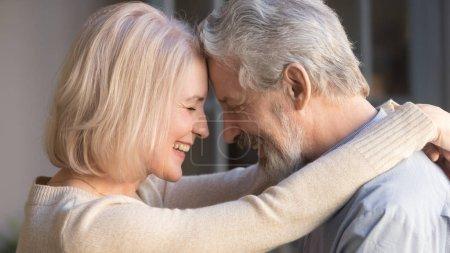Photo pour Aimer vieux couple de famille aîné collage embrassant toucher les fronts, romantique d'âge moyen mature homme et femme câlins se rapprocher profiter moment d'affection câlins, vue de côté de près - image libre de droit