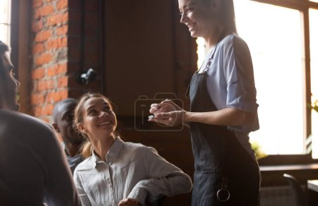 Photo for Happy female waitress holding notepad taking order serving clients in cafe pub restaurant, polite serving staff worker talking to guests diverse friends group choose food and drinks, customer service - Royalty Free Image
