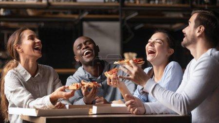 Photo pour Heureux amis divers riant à la blague drôle se réunissent à table partager le repas du déjeuner, groupe de jeunes gens joyeux manger de la pizza sur le dîner de fête, étudiants multiraciaux parler en s'amusant ensemble à la réunion - image libre de droit