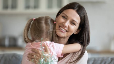Photo for Beautiful female holding white field pretty flowers hug little daughter looking at camera, concept of loving child attentive to parent, congratulation celebration of mothers or international women day - Royalty Free Image