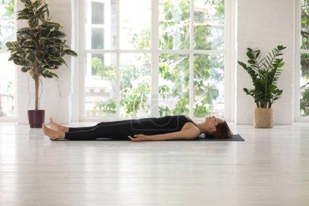 Photo pour Jeune femme portant des vêtements de sport noirs faisant de l'exercice Savasana, relaxant dans Dead Body, pose de cadavre, pratique du yoga, belle fille sportive travaillant à la maison ou dans un studio de yoga avec fenêtre et plantes - image libre de droit