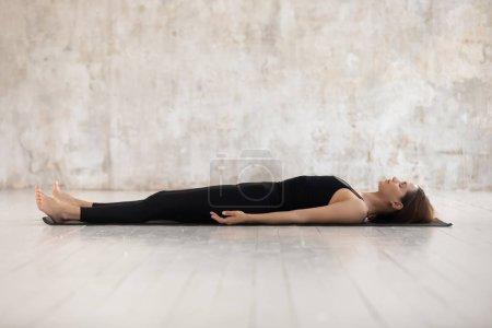 Photo pour Jeune femme portant des vêtements de sport noirs pratiquant le yoga, faisant du cadavre, exercice Savasana, relaxant, allongé dans la pose du corps mort sur le tapis, fille sportive travaillant à la maison ou dans un studio de yoga avec des murs gris - image libre de droit