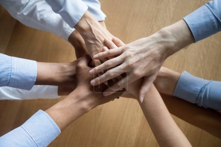 Top view of colleagues join hands motivated for shared success