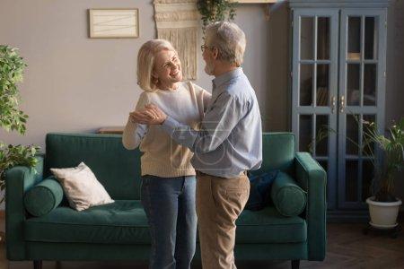 Photo pour Heureux couple d'amour mature dansant dans le salon se relaxant à la maison le week-end ensemble, souriant mari âgé aux cheveux gris et femme passer du temps valse étreignant embrasser, les conjoints profiter d'un rendez-vous romantique - image libre de droit