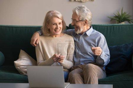 Photo pour Heureux conjoints retraités âgés assis sur le canapé passer le week-end à la maison ensemble regarder le film sur ordinateur portable, souriant mature mari et femme profiter de la vidéo sur ordinateur, utiliser Internet sans fil, nouvelles technologies - image libre de droit