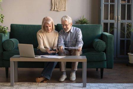 Photo pour Souriant conjoints de personnes âgées contemporaines utilisent ordinateur portable nouvelles technologies payer des factures bancaires en ligne, heureux mari et femme mûrs modernes calculer les finances, gérer les dépenses domestiques à la maison - image libre de droit