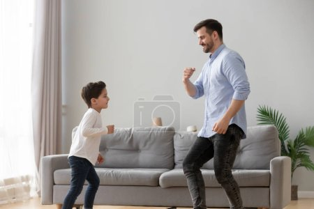Photo for Happy active family young dad and cute little kid son dancing having fun in living room together, funny preschool small boy laughing imitating father moves, daddy child play at home leisure lifestyle - Royalty Free Image