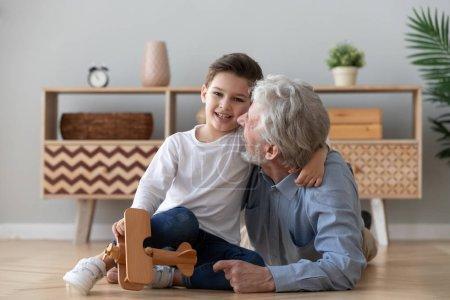 Photo pour Heureux vieux grand-père aimant embrassant mignon petit-fils regardant la caméra, deux générations de famille grand-père aîné et petit-enfant jouant avion en bois s'amusant collage sur le sol à la maison, portrait - image libre de droit