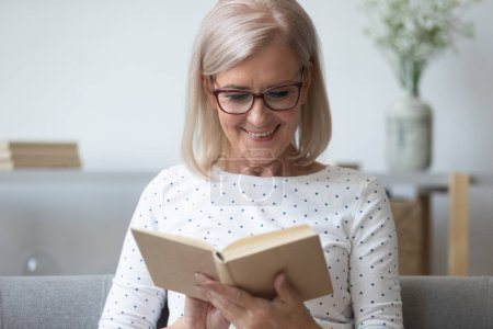 Photo for Smiling mature woman in glasses reading book close up, older female in spectacles enjoying interesting literature, favorite novel or poetry, resting on weekend at home, sitting on comfortable couch - Royalty Free Image