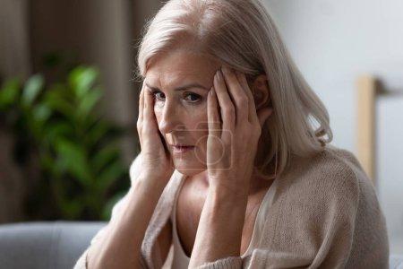 Photo pour Femme âgée bouleversée touchant des temples, se sentant mal, pression, s'asseyant seule, désordre mental ou démence, femelle mûre frustrée regardant dans la distance, pensant au problème émotif ou de santé - image libre de droit
