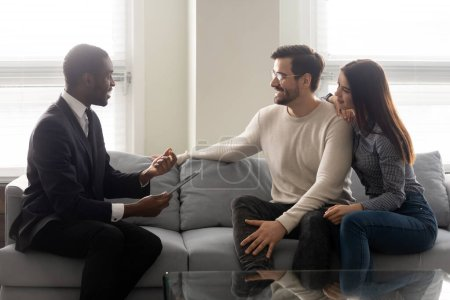 Photo pour Vue de côté heureux jeune couple familial assis sur le canapé, à l'écoute de l'offre d'experts financiers afro-américains excités. Agent immobilier mixte souriant expliquant les détails du contrat avec les clients . - image libre de droit