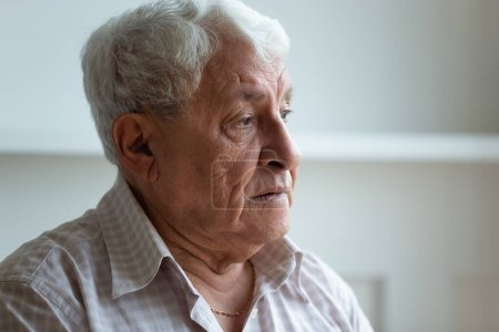 Photo for Elderly man feels sad and lonely looks away close up face, grey haired 70s grandfather thinking about disease or recollect life in nursing home care, concept of medicine for seniors, medical insurance - Royalty Free Image