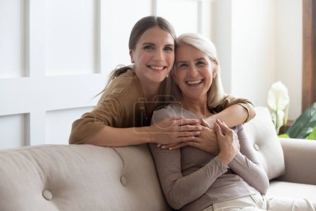 Photo pour Une adulte adorable dans les années trente une fille embrasse une mère âgée par derrière tandis qu'une mère assise sur un divan des gens posant devant la caméra le sourire se sent heureux, concept de famille multigénérationnelle, personne relativement dévouée - image libre de droit