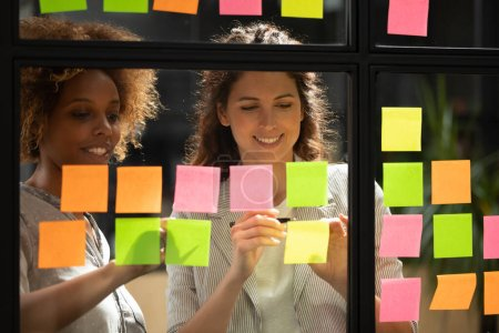 Photo for Pretty women colleagues work on project present ideas on post-it sticky notes attached on office glass wall, multiracial girls workers develop startup, brainstorming sharing thoughts. Teamwork concept - Royalty Free Image