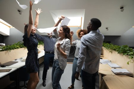 Photo for Highly successful multi-ethnic office workers scream with joy raise hands throwing papers celebrating accomplishment of project, financial success, got unbelievable opportunities career growth concept - Royalty Free Image