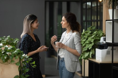 Photo for Asian and Caucasian ethnicity businesswoman talking discuss common project standing in workplace hall more experienced employee share knowledge with intern during coffee break in modern office hallway - Royalty Free Image