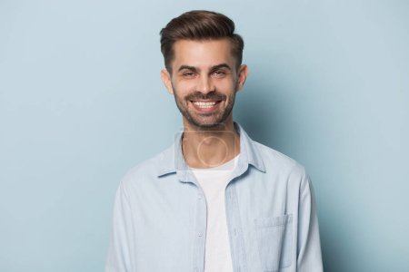 Photo for Close up headshot portrait of smiling Caucasian young man in shirt isolated on blue studio background look at camera, happy millennial guy model posing show white healthy teeth, dentistry concept - Royalty Free Image