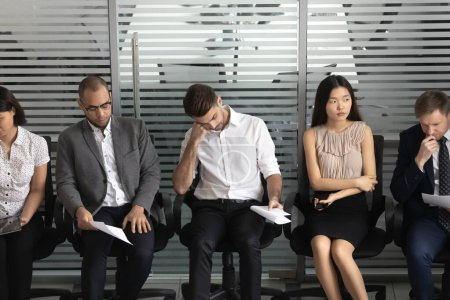 Photo for Diverse vacancy candidates waiting for job interview, multiracial people sitting in row on office chairs, using gadgets, smartphone, tablet, holding documents resume cv, employment process close up - Royalty Free Image