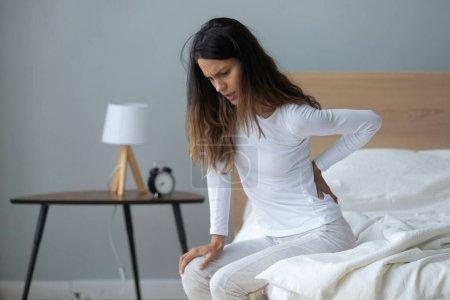 Photo pour Malsain malheureux millénaire mixte femme assise sur le lit, massant le dos, souffrant de sentiments douloureux, se réveillant le matin après avoir dormi sur un matelas inconfortable à la maison ou dans la chambre d'hôtel . - image libre de droit
