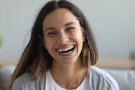 Photo pour Gros plan portrait de la tête souriant joli millénaire mixte jeune fille se réjouir. Heureux positif attrayant jeune femme rire, s'amuser, entendre de bonnes nouvelles, regarder la caméra . - image libre de droit