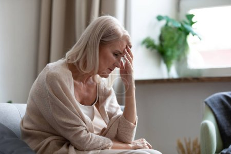 Photo for Sad depressed middle aged mature woman sitting alone at home touching head feeling headache migraine, upset tired old senior lady widow mourning suffer from grief loneliness mental problems concept - Royalty Free Image