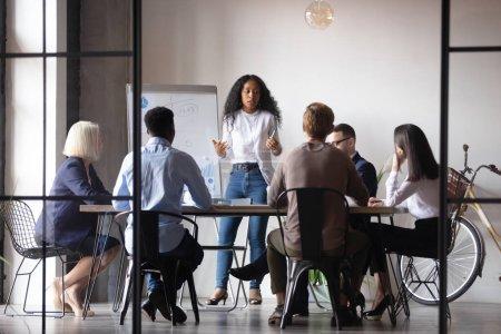 Selbstbewusste afrikanische Geschäftsfrau moderiert Whiteboard-Präsentation für Unternehmen